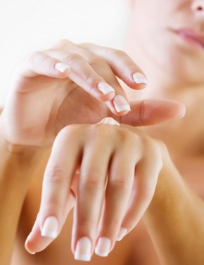 closeup of female hands applying hand cream